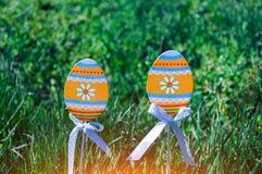 Uova di Pasqua sui bastoni di legno e sull'erba verde fotografie stock