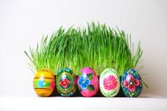 Uova di Pasqua Supporto in una linea Dietro loro l'erba verde Fotografia Stock