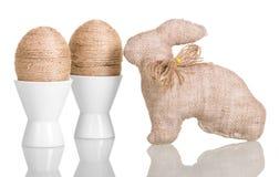 Uova di Pasqua in tazze con corda intrecciata ed il coniglietto isolato Immagini Stock Libere da Diritti