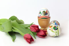 Uova di Pasqua in tazze ed in tulipani rossi Fotografia Stock