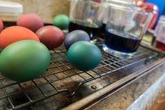 Uova di Pasqua tinte che si asciugano su uno scaffale Immagini Stock