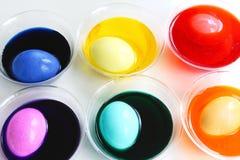 Uova di Pasqua di tintura in tazze di plastica Fotografia Stock