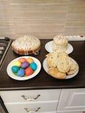 Uova di Pasqua, torte e panini con l'uva passa immagini stock