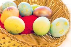 Uova di Pasqua in un canestro con una pietra in Immagine Stock Libera da Diritti