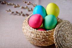 Uova di Pasqua in un canestro di vimini con i ramoscelli del salice Fotografie Stock