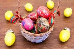 Uova di Pasqua in un canestro su un vecchio di legno Immagine Stock