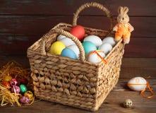 Uova di Pasqua in un coniglietto del giocattolo del canestro Fotografia Stock Libera da Diritti