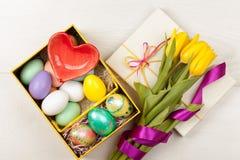 Uova di Pasqua in un contenitore di regalo con i tulipani gialli variopinti Fotografia Stock