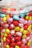 Uova di Pasqua in un fondo multicolore del barattolo di vetro della caramella Fotografie Stock