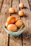 Uova di Pasqua in una ciotola blu su legno d'annata rustico Immagini Stock