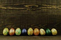 Uova di Pasqua in una fila su un fondo di legno marrone scuro, spazio della copia immagine stock
