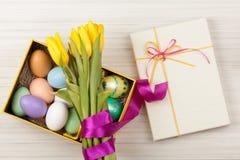 Uova di Pasqua in una scatola con i tulipani gialli variopinti Immagini Stock Libere da Diritti