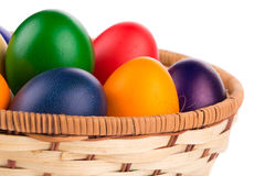 Uova di Pasqua variopinte in cestino Immagini Stock