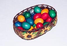 Uova di Pasqua variopinte in cestino Pasqua felice, religiou cristiano Fotografie Stock Libere da Diritti