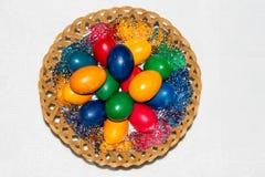 Uova di Pasqua variopinte in cestino Pasqua felice, religiou cristiano Fotografia Stock