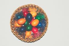 Uova di Pasqua variopinte in cestino Pasqua felice, religiou cristiano Immagini Stock Libere da Diritti