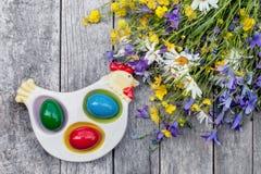 Uova di Pasqua variopinte che si trovano sul piatto sotto forma di pollo su un fondo di legno con un mazzo delle margherite dei f Fotografie Stock