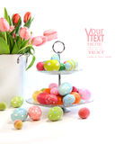 Uova di Pasqua variopinte con i tulipani dentellare su bianco Fotografia Stock