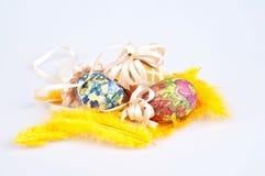 Uova di Pasqua variopinte con il nastro sulle piume Immagini Stock
