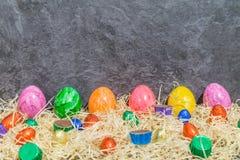 Uova di Pasqua variopinte con le uova di Pasqua del cioccolato e la carne dolce su fieno davanti a fondo grigio Fotografie Stock