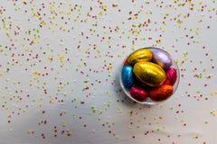 Uova di Pasqua variopinte del cioccolato in una ciotola trasparente con fondo bianco e coriandoli vaghi fotografia stock