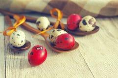 Uova di Pasqua variopinte della quaglia in cucchiai di legno Immagini Stock