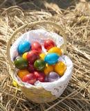 Uova di Pasqua variopinte dentro il vimine della paglia, su paglia Fotografie Stock