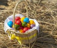 Uova di Pasqua variopinte dentro il vimine della paglia, su paglia Fotografie Stock Libere da Diritti