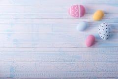 Uova di Pasqua variopinte dipinte a mano su un fondo blu Carta della molla di festa immagini stock