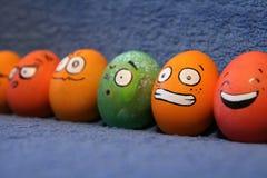 Uova di Pasqua variopinte divertenti con i fronti Immagine Stock