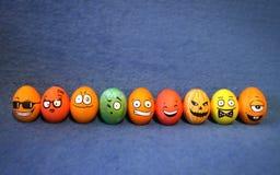 9 uova di Pasqua variopinte divertenti con i fronti Fotografia Stock Libera da Diritti