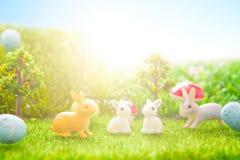 Uova di Pasqua variopinte e giocattoli dei conigli su erba verde Ambiti di provenienza astratti di fantasia con il libro magico Fotografia Stock Libera da Diritti