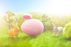 Uova di Pasqua variopinte e giocattoli dei conigli su erba verde Ambiti di provenienza astratti di fantasia con il libro magico Immagine Stock