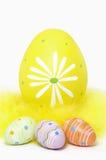 Uova di Pasqua Variopinte e piume gialle su fondo bianco fotografie stock
