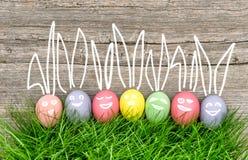 Uova di Pasqua variopinte in erba verde Decorazione divertente Immagini Stock Libere da Diritti