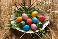 uova di Pasqua variopinte luminose su un piatto bianco ovale circondato da erba verde Vista da sopra fotografia stock libera da diritti