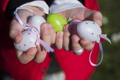 Uova di Pasqua variopinte in mani dei bambini Immagini Stock