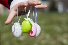 Uova di Pasqua variopinte in mani dei bambini Fotografia Stock Libera da Diritti