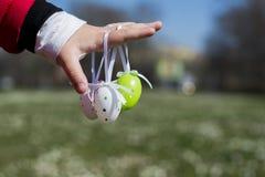 Uova di Pasqua variopinte in mani dei bambini Fotografia Stock