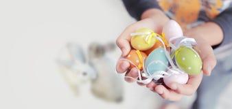 Uova di Pasqua variopinte in mani del bambino Fotografia Stock