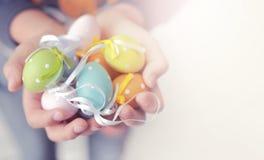 Uova di Pasqua variopinte in mani del bambino con lo spazio della copia per i testi, così Immagini Stock
