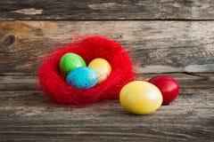 Uova di Pasqua variopinte in nido rosso fotografia stock libera da diritti