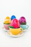 Uova di Pasqua variopinte in piccole tazze Fotografie Stock