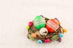 Uova di Pasqua variopinte in piccolo nido su fondo leggero Fotografia Stock