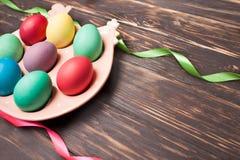 Uova di Pasqua variopinte sulla disposizione ceramica del pollo per le uova su fondo di legno Concetto di celebrazione di Pasqua  Fotografia Stock