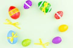 Uova di Pasqua variopinte sulla disposizione verde pastello del piano del fondo Copi lo spazio Fotografia Stock