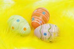 Uova di Pasqua Variopinte sulle piume gialle immagini stock