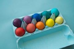 Uova di Pasqua variopinte tinte mano vibrante in una scatola delle uova del cartone osservata Fotografia Stock Libera da Diritti