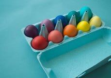 Uova di Pasqua variopinte tinte mano vibrante in una scatola delle uova del cartone osservata Immagini Stock Libere da Diritti