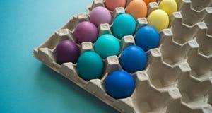 Uova di Pasqua variopinte tinte mano vibrante in una scatola delle uova del cartone osservata Fotografie Stock Libere da Diritti